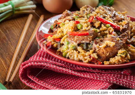 Fried rice with chicken and vegetables served on a 65831970