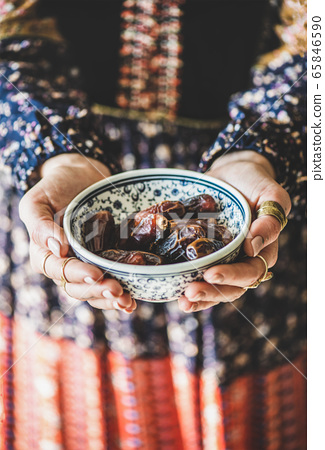 Woman in oriental dress holding bowl of dates for 65846590
