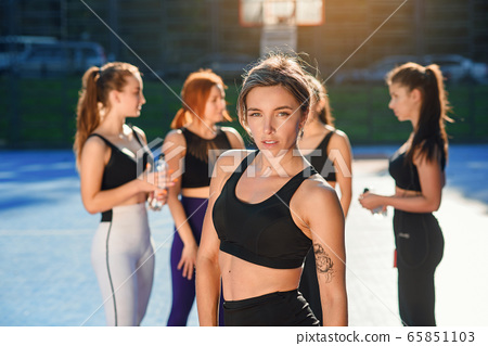 Front view of charming smiling sporty slim lady looking at camera after ending her sport training on the specially equipped sportground in the urban park 65851103