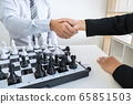 Businessman and businesswoman shaking hands after 65851503