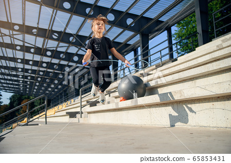 happy girl jumping with skipping rope outdoor 65853431