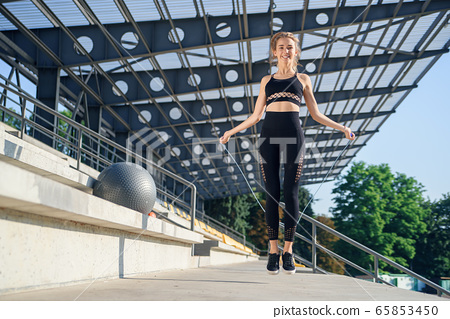 Woman jumping with skipping rope at stadium. Active fitness female doing exercises outdoor. Fitness concept. Healthy lifestyle. 65853450
