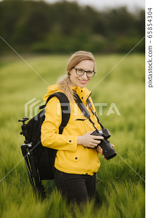 Charming lady standing at wheat field with digital camera 65854304