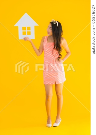Portrait beautiful young asian woman show home or house sign 65856627