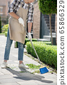 Male in protective gloves and apron sweeping leaves with broom in the yard 65866329