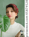 Portrait of a young beautiful woman with perfect smooth skin with a large green tropical leaf. Fashion, beauty, makeup, cosmetics, health, ecology, nature, spa, wellness. 65874528