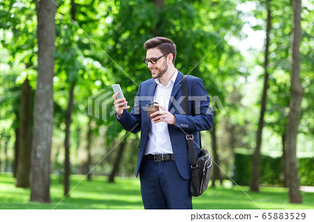 Attractive business executive with takeaway coffee browsing internet in green park 65883529