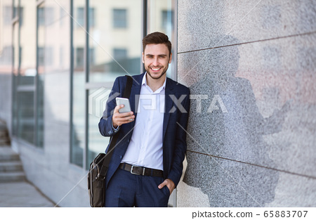 Corporate employee with cellphone standing near office tower on city street 65883707