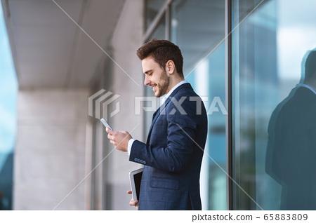 Confident young enterpreneur using his cellphone for online communication near business center 65883809