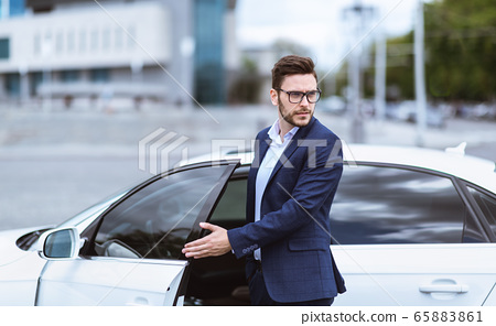 Confident businessman getting out of his car in urban city 65883861