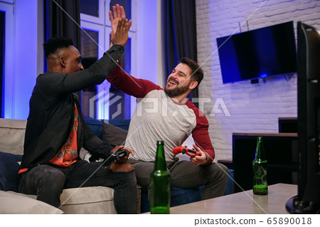 friends at home playing video game sitting on couch holding controllers 65890018
