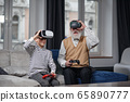 Portrait of excited senior man using VR glasses sitting on sofa at home with laughing grandson beside him 65890777
