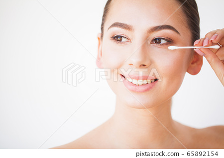 Young woman contouring her eyebrows with cotton swab 65892154