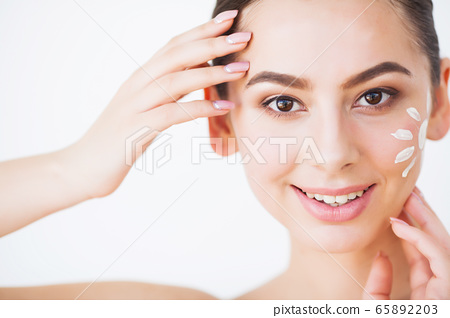 Beautiful woman using a skin care product, moisturizer or lotion and Skin Care taking care of her dry complexion. 65892203