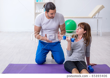 Young woman doing sport exercises with personal coach 65893406