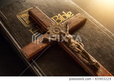 Closeup of wooden Christian cross on Bible. 65903229