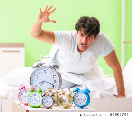Young man having trouble waking up in early morning 65903748