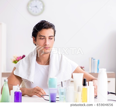 Young handsome man in the bathroom in hygiene concept 65904656