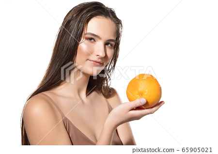 Close up of beautiful female face with orange over white background. Cosmetics and makeup, natural and eco treatment, skin care. 65905021