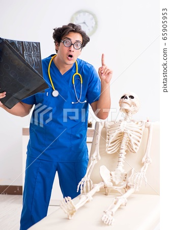 Funny doctor with skeleton in hospital 65905953