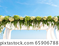 Wedding decoration with a luxurious arch of fresh flowers on a sunny day. Close-up. Copy space. 65906788