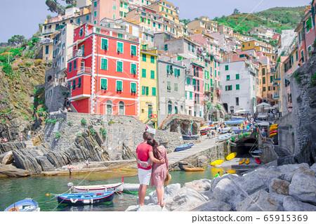Tourists looking at scenic view of Riomaggiore, Cinque Terre, Liguria, Italy 65915369