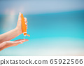 Closeup suncream bottle in female hands background turquoise water 65922566