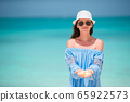 Young fashion woman in green dress on the beach 65922573