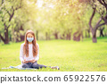 Little girl with dog wearing protective medical mask for prevent virus outdoors in the park 65922576