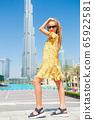 Happy girl walking in Dubai with skyscraper in the background. 65922581