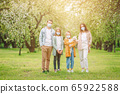 Adorable family in blooming cherry garden in masks 65922588