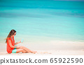 Beautiful young woman holding a suncream lying on tropical beach 65922590
