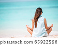 Young fashion woman in green dress on the beach 65922596