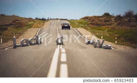 Road with stone letters LOCKDOWN. The letters are in disarray on the track. The concept of ending quarantine 65923403