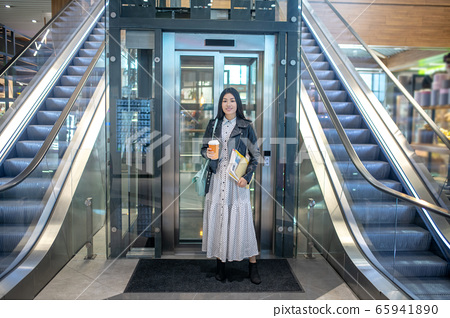 Young brunette female standing with coffee cup and papers in front of the elevator, smiling 65941890