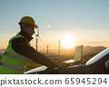 Technician Engineer in Wind Turbine Power Generator Station checks the status of the turbines using a laptop 65945294