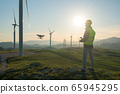 Technician Engineer in Wind Turbine Power Generator Station launches a drone for visual control of generators 65945295