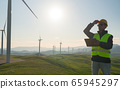 Technician Engineer in Wind Turbine Power Generator Station standing with a tablet in his hands 65945297