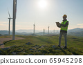 Technician Engineer in Wind Turbine Power Generator Station standing with a tablet in his hands 65945298