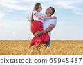 Young man holding beloved in his hands in wheat 65945487