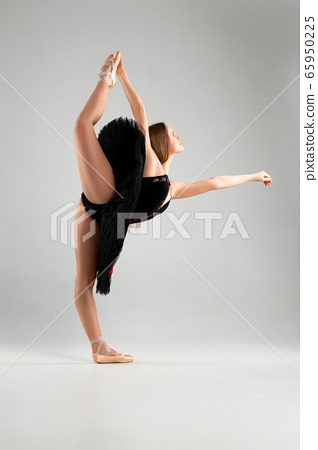 Girl in a black ballet dress. Ballerina in a dark ballet tutu on a light background. The young ballerina is warming up 65950225