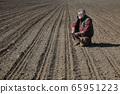 Farmer in field after sowing analyze land 65951223