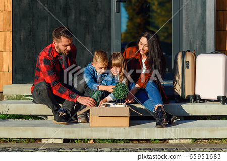 Satisfied young parents with their happy children sitting on new house's stairs and get from the carton box green flower pots and clock. New stylish cozy home of lovely family near forest. 65951683