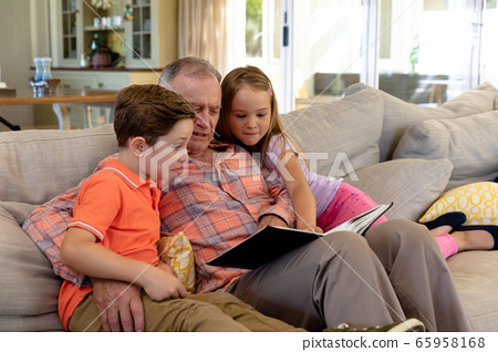 Grandfather and grandchildren at home in the living room 65958168
