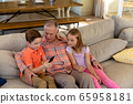 Grandfather and grandchildren at home in the living room 65958181