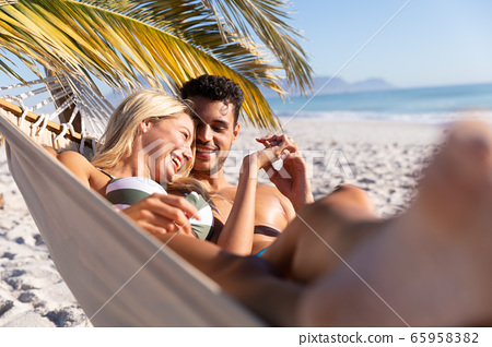 Caucasian couple lying on a hammock at the beach. 65958382