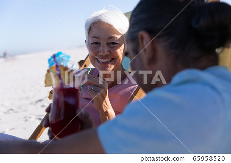 Senior Caucasian couple sitting on deck chairs at the beach. 65958520