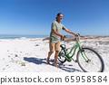 Senior Caucasian man carrying a bike at the beach 65958584
