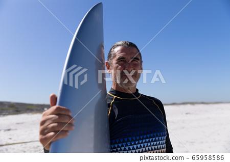 Senior Caucasian man holding a surfboard at the beach. 65958586