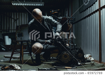 Young man repairing his motorcycle engine in the garage. The motorcycle engine is disassembled. Motor capital repair. Sixteen valves and four cylinder.  65972789